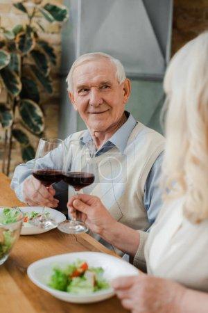 Photo pour Heureux couple de personnes âgées dîner avec du vin et de la salade à la maison en quarantaine - image libre de droit