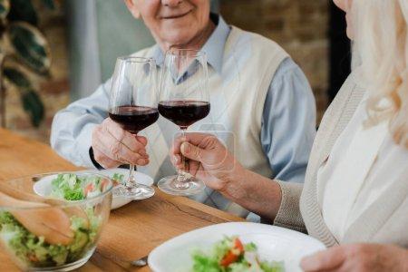 Photo pour Vue recadrée du couple âgé dînant avec du vin et de la salade à la maison sur l'isolement - image libre de droit