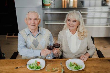 Photo pour Heureux couple de personnes âgées dîner avec du vin et de la salade à la maison sur l'isolement - image libre de droit
