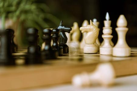 Photo for Detail view of chess pieces knights facing each other for a standoff on chessboard - Royalty Free Image