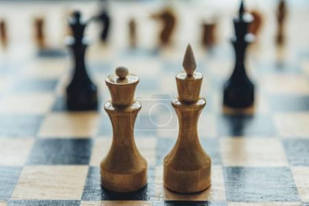 Photo pour Vue rapprochée des figures blanches du roi et de la reine des échecs sur l'échiquier - image libre de droit