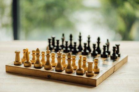 Photo pour Vieil échiquier prêt pour un nouveau match sur la table. Focus sélectif sur les figures d'échecs blanches - image libre de droit