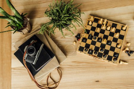 Photo for Above view of chess board with chess pieces, potted plant and vintage camera on the top of books - Royalty Free Image