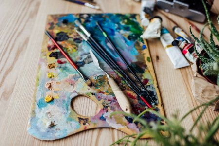 Photo for High angle view of artist palette with paint brushes, palette knife and oil paint tubes on the table - Royalty Free Image
