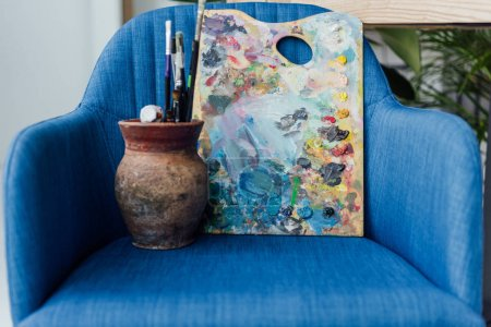 Photo for Creative jar filled with paint brushes and palette of artist staying on blue armchair - Royalty Free Image