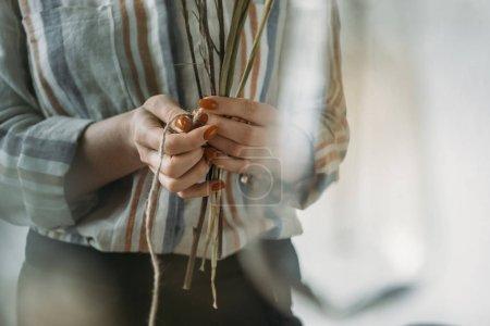 Foto de Recorta la vista de las manos femeninas con flores secas en el lugar de trabajo - Imagen libre de derechos