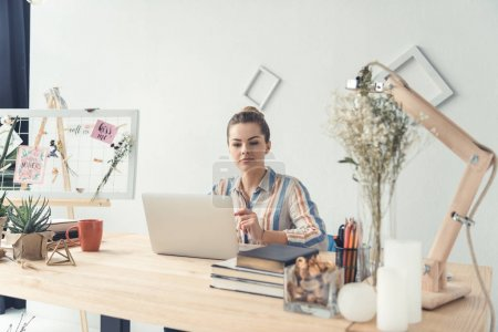 Photo for Attractive businesswoman working with laptop while sitting at table in modern office - Royalty Free Image