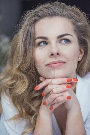 Photo for Portrait of beautiful blonde dreamy woman with red manicure - Royalty Free Image
