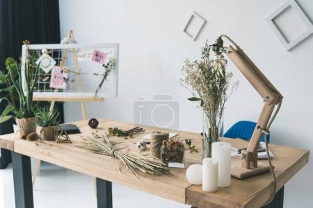 Photo for Florist workplace with board, dry flowers and wheat ears in modern office - Royalty Free Image
