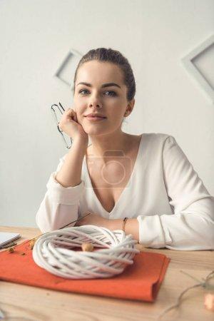 Photo pour Souriante bel femelle décorateur avec couronne blanche au milieu de travail - image libre de droit