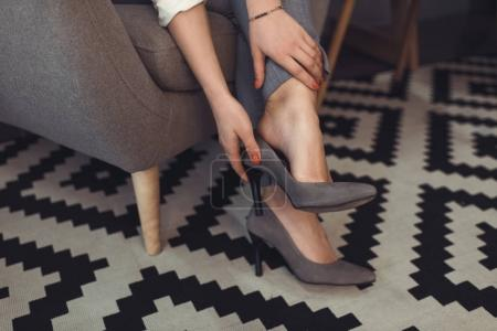Photo for Cropped view of stylish tired woman taking off her heels - Royalty Free Image