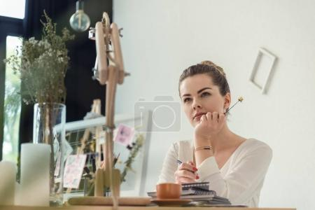 Photo for Pensive attractive female florist holding dry flower and sitting in creative office - Royalty Free Image