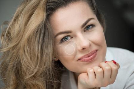 Photo pour Portrait de femme blonde heureuse en vêtements blancs souriant à la caméra - image libre de droit