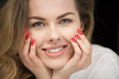 Photo pour Portrait de jolie femme souriante avec manucure rouge regarder la caméra - image libre de droit