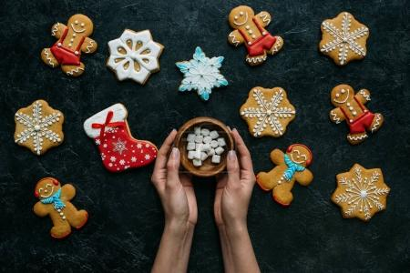 hands with marshmallows and gingerbreads