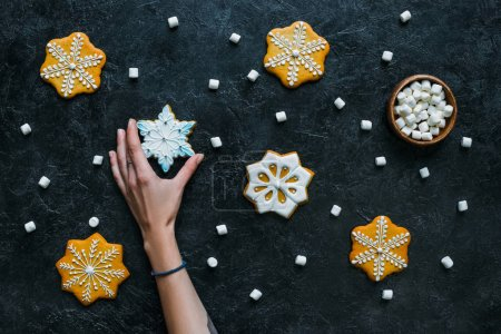 hand with gingerbread snowflakes and marshmallows