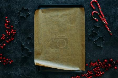 Photo for Top view of cookie cutters around baking tray with copy space on black tabletop - Royalty Free Image