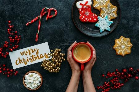 Photo for Cropped view of female hands with gingerbreads, coffee and merry christmas greeting card on black tabletop - Royalty Free Image