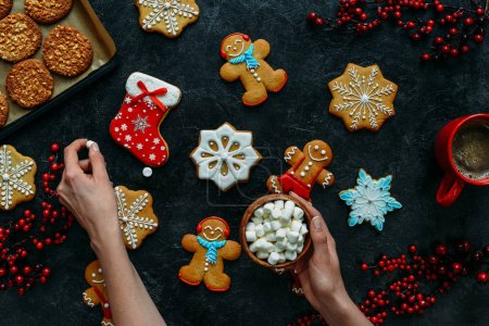christmas gingerbreads and marshmallows in hands