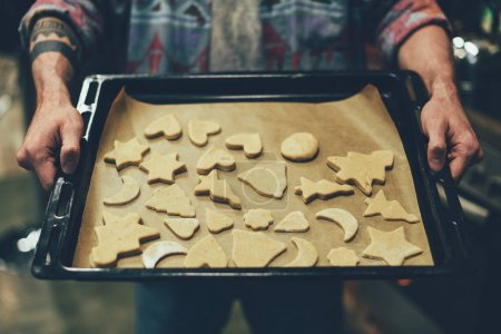 Photo for Partial view of person holding cookie tray with delicious christmas cookies - Royalty Free Image