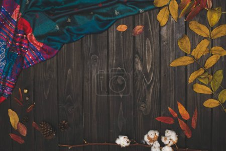 Photo for Top view of beautiful autumn leaves and fabric on wooden surface - Royalty Free Image