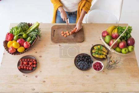 Photo for Partial view of woman cutting fresh carrot on wooden cutting board at table - Royalty Free Image