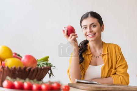 Photo for Portrait of beautiful smiling woman with fresh apple in hand sitting at table - Royalty Free Image