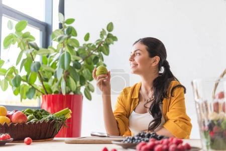 Photo for Side view of beautiful smiling woman with fresh apple in hand sitting at table - Royalty Free Image