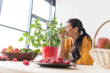 Photo for Side view of beautiful smiling woman with fresh apple in hand sitting at table and looking out window - Royalty Free Image