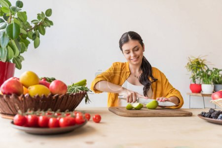 Photo for Portrait of young woman cutting fresh apple on wooden cutting board at table - Royalty Free Image