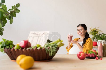 Photo for Selective focus of beautiful pregnant woman with detox drink in hand sitting at table with organic food - Royalty Free Image