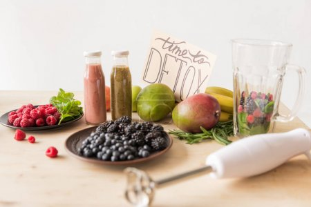 Photo for Selective focus of detox drinks, time to detox card, blender and organic food on wooden table - Royalty Free Image