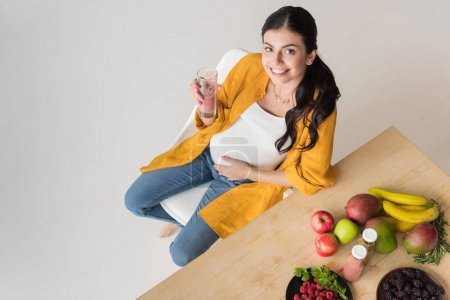 Photo for High angle view of smiling pregnant woman with detox drink looking at camera while sitting at table - Royalty Free Image