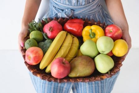 Photo for Cropped shot of woman holding basket with fresh vegetables and fruits in hands - Royalty Free Image