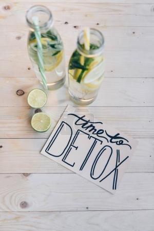 Photo for Top view of time to detox card and detox drinks with citrus on wooden tabletop - Royalty Free Image