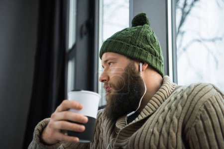 Man holding thermos cup