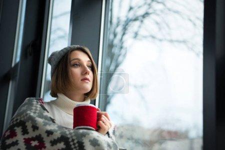 Photo pour Fille en vêtements d'hiver tenant tasse de thé rouge et regardant loin - image libre de droit