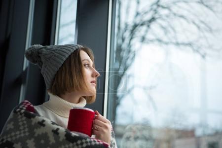 Photo pour Fille tenant une tasse de thé rouge et regardant la fenêtre - image libre de droit