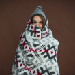 Woman standing wrapped in blanket and wearing gray...