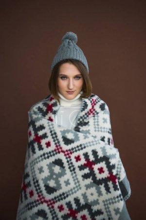 Photo pour Fille enveloppée dans une couverture et portant un chapeau gris isolé sur brun - image libre de droit
