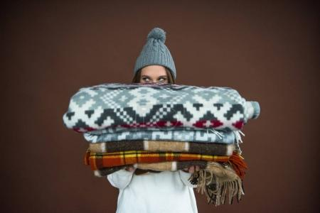 Photo pour Femme regardant hors de la pile de couvertures dans ses mains - image libre de droit