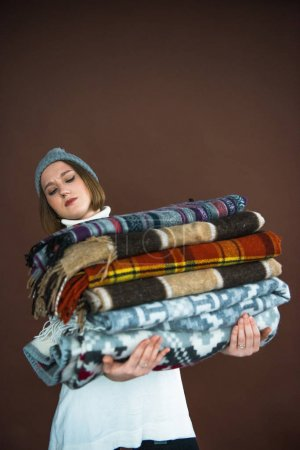 Woman holding heavy pile of blankets