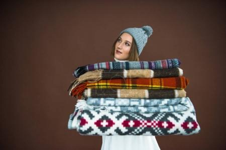 Woman holding pile of blankets