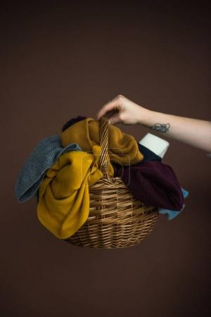 Photo for Cropped image of woman holding wicker basket with pile of hats and scarfs isolated on brown - Royalty Free Image