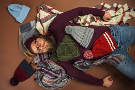 Photo for Top view of man lying on blankets covered by winter hats isolated on brown - Royalty Free Image
