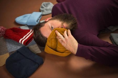 Man covering face with hat