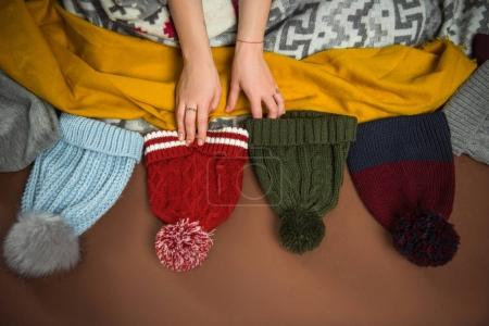 Photo for Cropped image of woman choosing winter hat on brown - Royalty Free Image