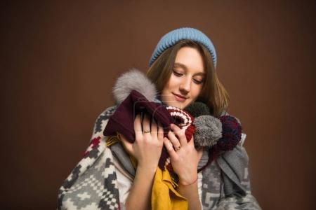 Girl holding winter hats