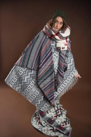 Photo pour Fille debout enveloppé dans des couvertures chaudes isolées sur brun - image libre de droit