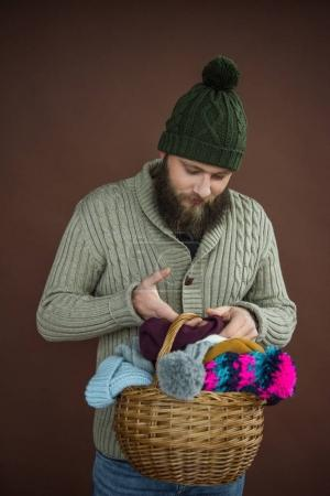 man holding basket with hats and scarfs